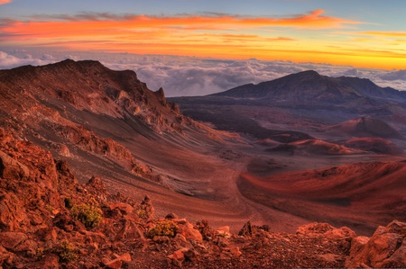 volcano slope: Volcanic crater landscape with beautiful orange clouds at sunrise taken at Haleakala National Park in Maui, Hawaii. Stock Photo
