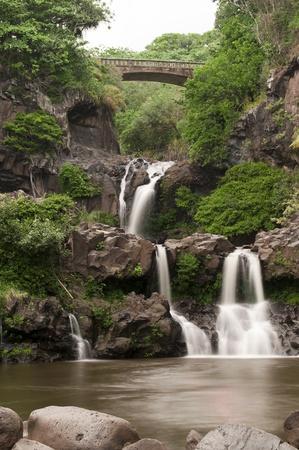 하나, 하와이 마우이에있는 일곱 신성한 풀. 여러 폭포와 녹색 식물과 바위와 스트림의 아름 다운 세로 오래 노출 사진.