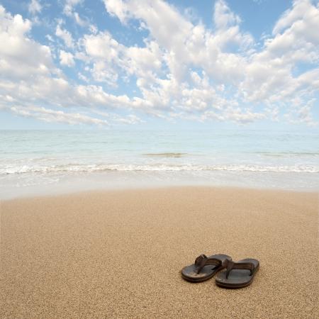 ビーチ サンダルやトング砂浜背景 copyspace たっぷりで 写真素材