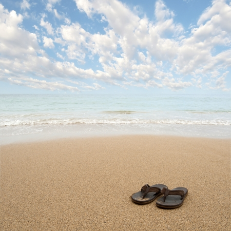 Beach sandals or tongs on a sandy beach with lots of background copyspace