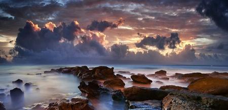 shining through: Seascape oceano bella con un dorato tramonto splende attraverso le nuvole Hawaii viola scure al crepuscolo Archivio Fotografico