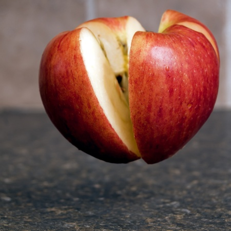 Red apple cut in four different peices floating above a kitchen counter top Foto de archivo