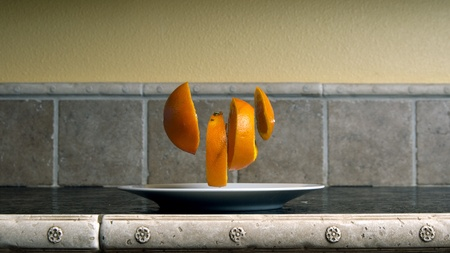 kitchen counter top: Four orange slices floating over a white dish on a kitchen counter top.