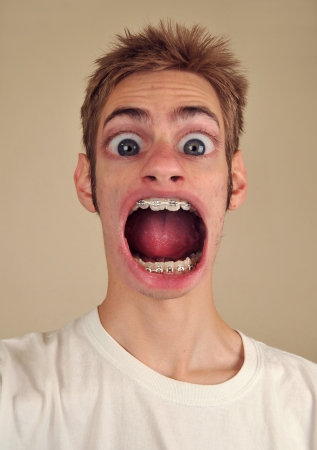 A young man screaming with huge eyes and mouth Foto de archivo