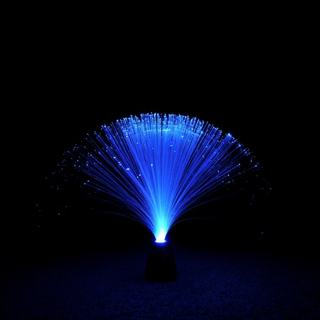 Blue fiber optic lamp resting on a carpet floor.