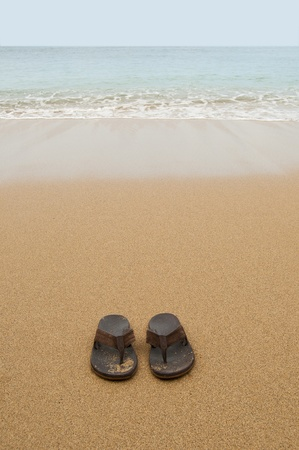 Beach sandals or tongs on a sandy beach with lots of background copyspace photo