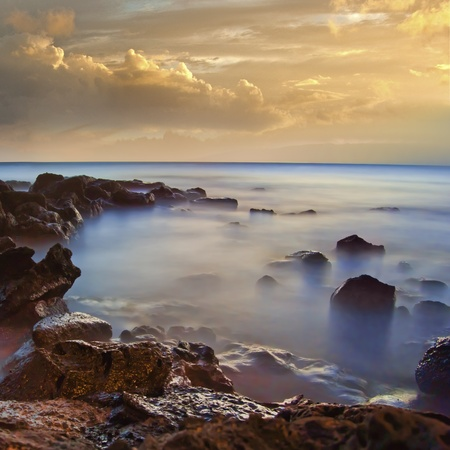 dramatic sunrise: Beautiful ocean seascape with a golden sky and red and blue colorful sea rocks with a foggy ocean mist creeping in the morning
