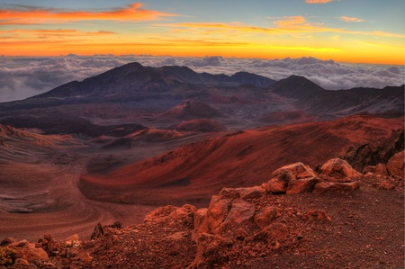 Volcanic crater landscape with beautiful orange clouds at sunrise taken at Haleakala National Park in Maui, Hawaii. Stock Photo