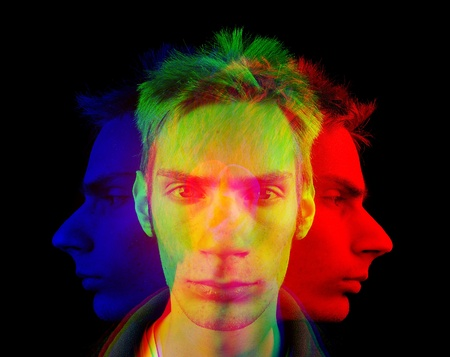 Futuristic or retro headshot portrait of a young man with the primary red, green, and blue colors mixed up around his head. This mastermind has multiple personalities and can see in different perspectives