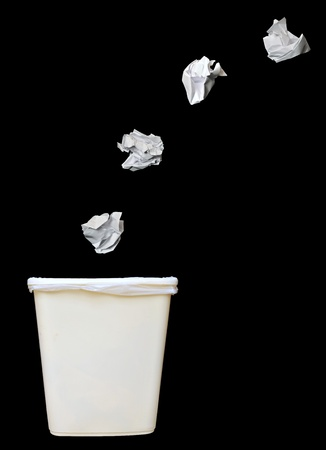 Bunch of crumbled paper being throwing into a trash bin or waste bin isolated on black background Reklamní fotografie - 9327828