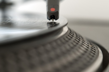 remix: DJ record turntable. Macro closeup of the needle on a 12 inch vinyl LP playing hiphop techno rave beats. Stock Photo