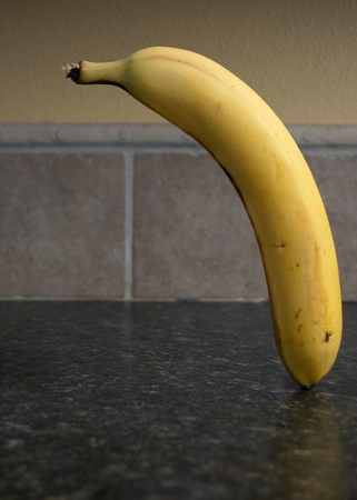 kitchen counter top: Banana floating over a plate chopped up over a kitchen counter top. Stock Photo