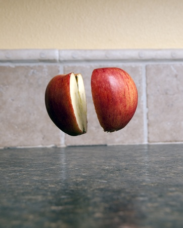 Red apple being cut in half with a sharp knife being held up by one single toothpick