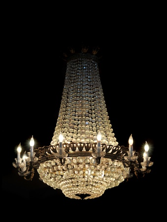 Chandelier lit up and isolated over a black background photo