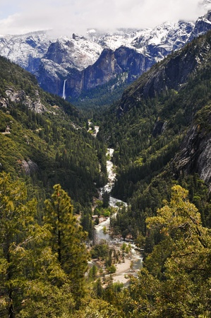 transforms: Snow on top of the mountain melts off and falls off the mountain as a water fall as it then transforms into a river and stream going into the forest. Yosemite national Park, California. Stock Photo