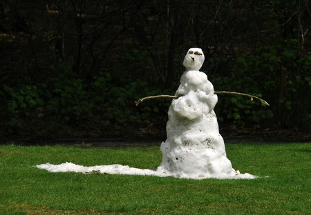 frosty the snowman: A sad snowman melting in the grass when the sun comes out