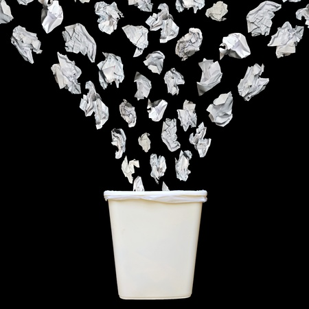 Bunch of cumbled paper being throwing into a trash bin or waste bin isolated on black background.
