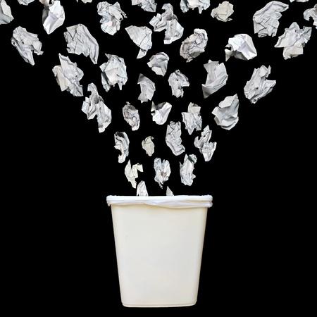 Bunch of cumbled Papier in einen Mülleimer oder Papierkorb isoliert auf schwarzem Hintergrund zu werfen.