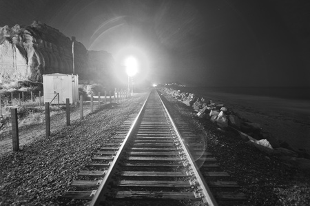 Train tracks at night with a train coming down the tracks. Photograph taken on the coastal shore in California. You can see the beach to the right