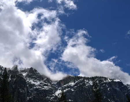 evaporating: Cloud formations appear to be evaporating off the snowy mountain. Stock Photo