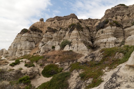 dropoff: Coastal geological cliffs with lines on the tops of them next to a California beach Stock Photo
