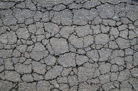 cracked: Macro closeup on concrete asphalt cracks on the road Stock Photo