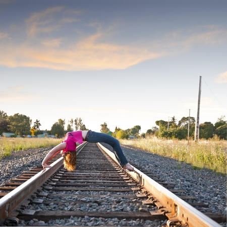 bridging: Young attractive female Arching Back over Railroad tracks