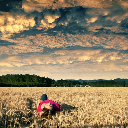 wheatfield: Attractive young teenage white Caucasian female watching clouds while floating above a beautiful golden field landscape
