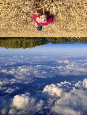 reverse: Attractive young teenage white Caucasian female floating above a beautiful field landscape with upside down clouds