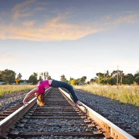 arching: Mujer joven y atractiva arquear la espalda sobre las v�as del ferrocarril Foto de archivo