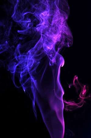 wisp: abstract illuminated purple Smoke isolated on a pitch black background