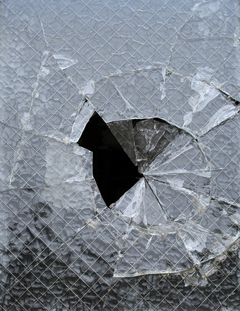 a peice of glass window with a cracked hole Stock Photo
