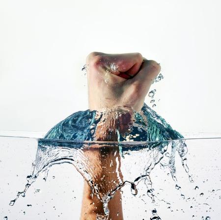 sumergido: Un pu�o que golpea el agua enojado aisladas sobre fondo blanco Foto de archivo