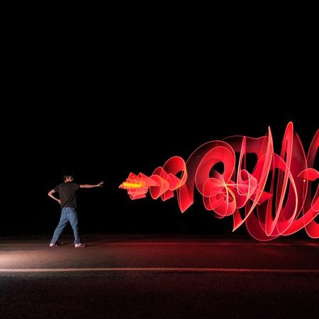 Een man in de straat in het midden van de nacht schieten van een graffiti-achtige kunst Laser Blast bevoegdheden uit zijn hand