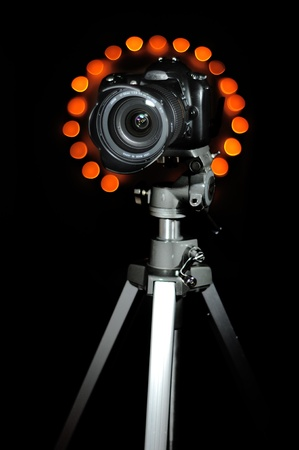tripod mounted: Camera on a tripod isolated on black background with bokeh circles in the background Stock Photo
