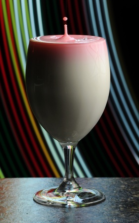 highspeed: Abstract shot of a wine glass filled with milk and a splashing highspeed droplet coming out of the top.