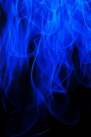An abstract blue flame long exposure background isolated over a black background.