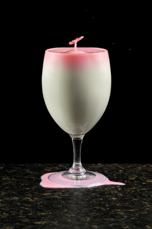full suspended: Abstract shot of a wine glass filled with milk and a splashing highspeed droplet coming out of the top.