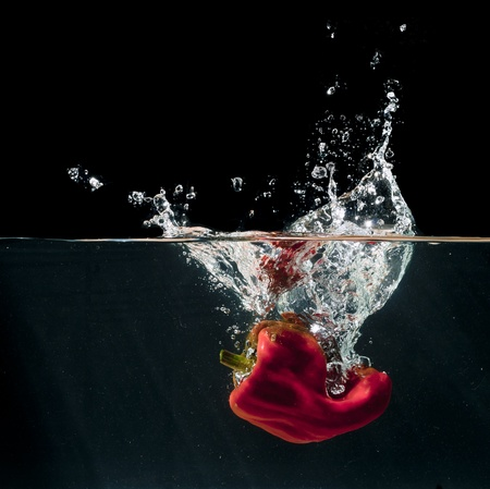 dispersion: A red hot pepper splashing into water isolated on black background