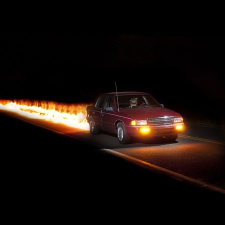 burning time: A red hot speed demon car racing down a road at night with no one inside of it.