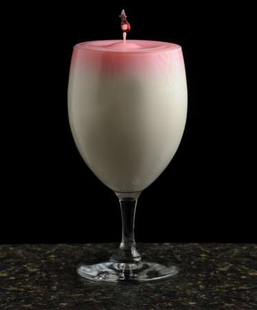 full suspended: Drop of liquid suspended above a glass full of creamy blended cocktail with a pink surface isolated on a black background Stock Photo