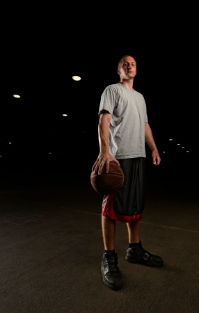 sports hall: Basketball player standing and looking at camera with ball in hand at night