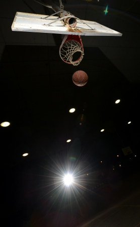 midair: Basketball hoop and ball in midair at night with lights turned on