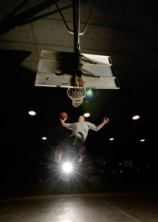 Basket and basektball player jumping with ball and aiming at basket with lights turned on at night photo
