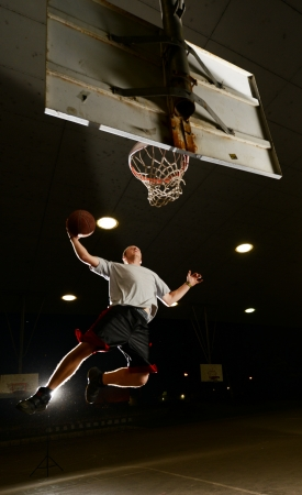 Basket and basektball player jumping with ball and aiming at basket at night photo