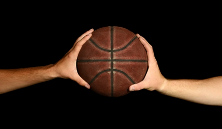 Two male hands holding basketball, image on black background.
