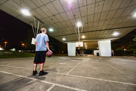 Young basketball player standing in outdoors covered court, ball in his hand and back to camera at night. photo