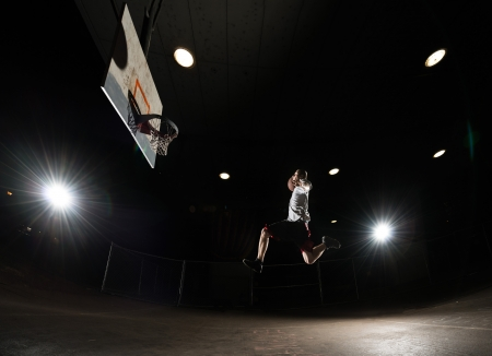 baller: Basketball player at night jumping and aiming at hoop with lights on Stock Photo