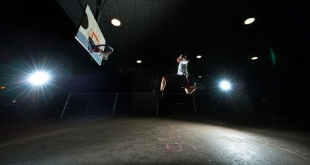 Basketball court at night with basketball player jumping and aiming at hoop
