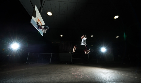 Basketball court at night with lights on, basketball player jumping and aiming at hoop photo